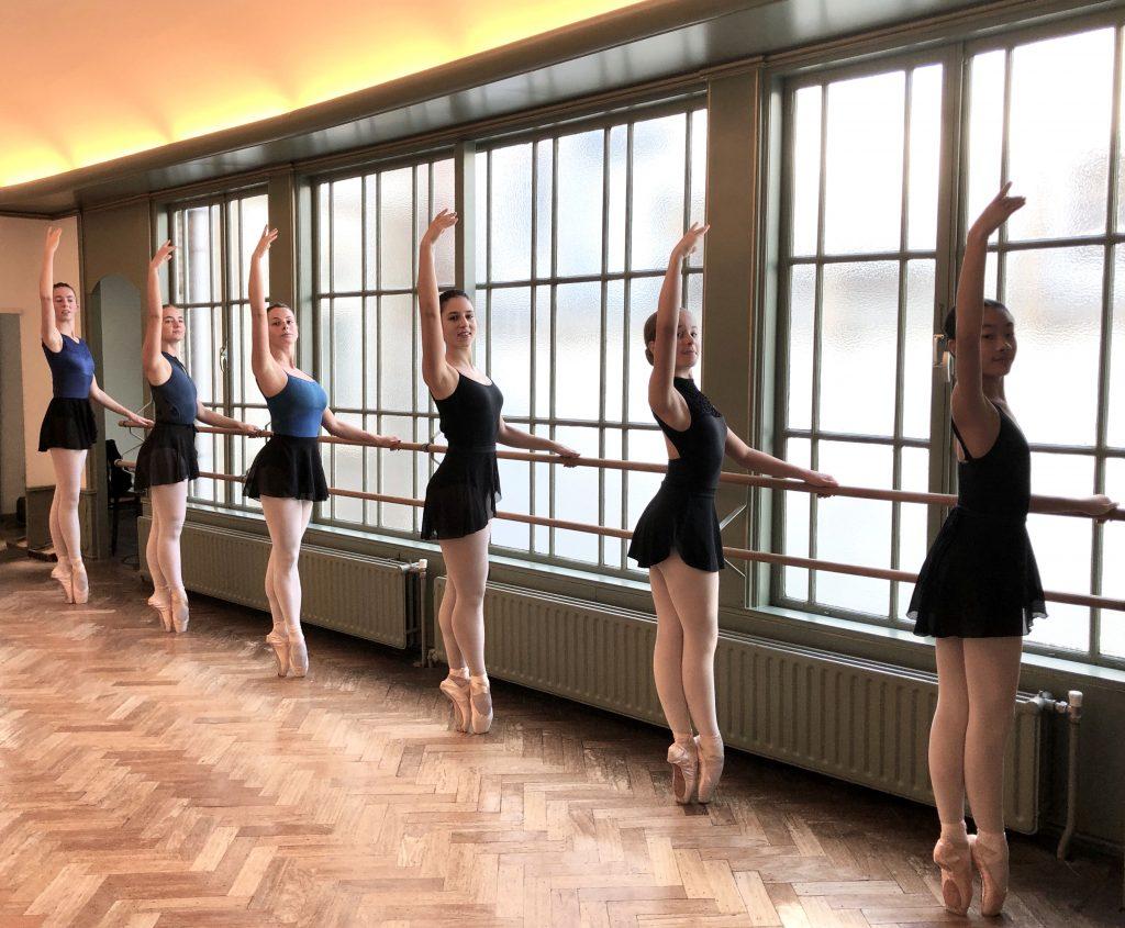 6 jonge dansers aan de barre op spitzen